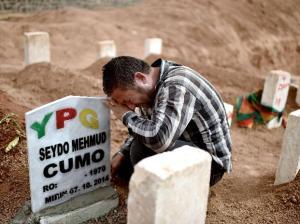 dolor. Un familiar llora ante la tumba de un miliciano kurdo en Turquía.